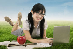Asian schoolgirl learns on meadow Royalty Free Stock Photography