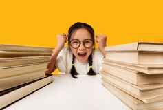 Free Asian Schoolgirl Shouting Crying Sitting At School Books, Yellow Background Stock Photos - 193832173