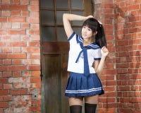 Asian schoolgirl standing in front of school Stock Photo
