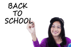 Asian schoolgirl writes Back to School Royalty Free Stock Image
