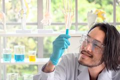 Asian scientist checking liquid substance in test tube stock images