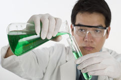 Asian Scientist doing research. Scientist pouring chemicals in a laboratory Stock Photos