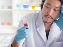 Asian scientist seriously analyze liquid substance stock image