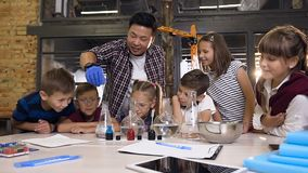 Asian scientist with six young children working with chemical reaction in chemistry lab. Chemical reaction blue color in stock video footage