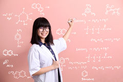 Asian scientist writing on pink wall Stock Photo