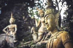 Asian sculptures symbolizing traditional culture and Buddhism in outdoors garden at sunset in Thailand. Asian statues symbolizing traditional culture and Royalty Free Stock Images