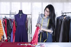 Asian seamstress cutting a fabric in the workplace. Portrait of Asian seamstress cutting a fabric by using scissor while standing in her workplace Stock Image
