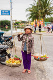 Asian seller carrying Rambutan mango banana and mandarin Royalty Free Stock Photos