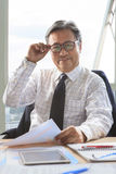 Asian senior business man relaxing on working table Stock Photo