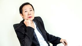 Asian senior business woman sit on chair thinking about manageme Stock Images