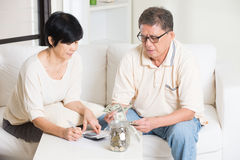 Asian senior couple calculating. Finance at their home stock photography