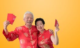 Asian senior couple celebrate Chinese new year in red traditional costume stock images