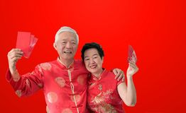 Asian senior couple celebrate Chinese new year in red traditional costume royalty free stock images