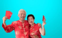 Asian senior couple celebrate Chinese new year in red traditional costume stock photo