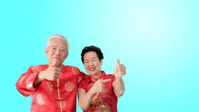 Asian senior couple celebrate Chinese new year in red traditional costume stock photography