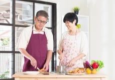 Asian senior couple cooking. At the kitchen Stock Photos