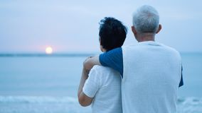 Asian senior couple dating at sunrise sea Stock Photos