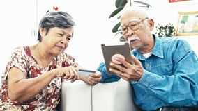 Asian Senior couple e-shopping with digital tablet. Dolly shot of Senior couple online shopping with smile face. 4K Slow motion stock video footage