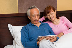 Asian senior couple enjoying in bed Royalty Free Stock Images