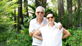 Asian senior couple with green tropical nature background Royalty Free Stock Photography