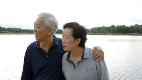 Asian senior couple happy hugging together lake background Royalty Free Stock Photo