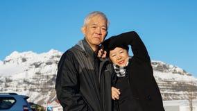 Asian senior couple have fun in Europe portrait with snow mountain background. Asian senior couple have fun in Europe portrait with snow mountain stock photo