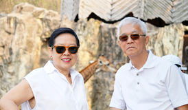 Asian senior couple have fun at zoo. looking at african animal Stock Image