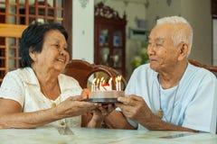 Asian senior couple holding a cake and smiling Stock Photos