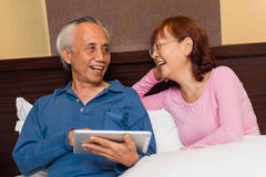 Asian senior couple laughing stock image