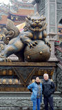 Asian senior couple with lion guardian of temple in Taiwan Royalty Free Stock Image