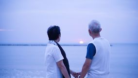 Asian senior couple dating at sunrise sea Stock Images
