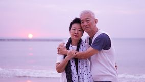 Asian senior couple dating at sunrise sea Royalty Free Stock Photos