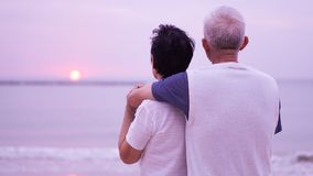 Asian senior couple dating at sunrise sea Royalty Free Stock Image
