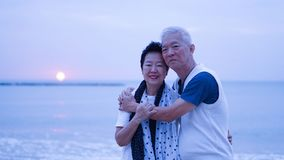 Asian senior couple dating at sunrise sea Royalty Free Stock Photography