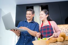 Asian senior couple online learning cooking together royalty free stock image