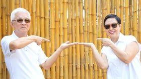 Asian senior couple present product with golden bamboo backgroun Stock Photo