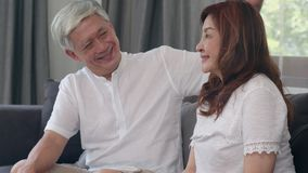 Asian senior couple relax at home. Asian Senior Chinese grandparents, husband and wife happy smile hug talking together while