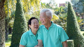 Asian senior couple relaxing in the park. Laughing in sunshine Stock Photo