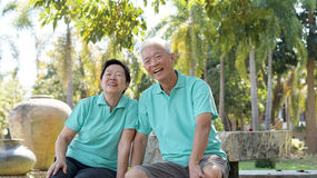 Asian senior couple relaxing in the park. Laughing in sunshine Royalty Free Stock Photos