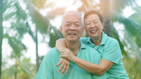 Asian senior couple relaxing in the park laughing in sunshine Royalty Free Stock Photography