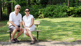 Asian senior couple sitting at bench in the park with copy space Royalty Free Stock Images