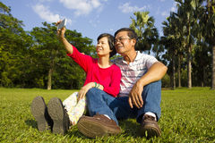 Asian Senior couple sitting on grassland and  taking picture Royalty Free Stock Images