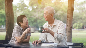 Asian senior couple start morning coffee in park, optimistic con Stock Images