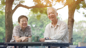 Asian senior couple start morning coffee in park, optimistic con Royalty Free Stock Images