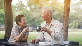 Asian senior couple start morning coffee in park, optimistic and Stock Photography