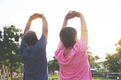 Asian elderly people stretching before exercise. Asian senior couple stretching before exercise at park outdoor Royalty Free Stock Image