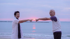 Asian senior couple together at sunrise beach. New year, new cha royalty free stock image