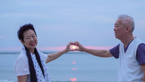 Asian senior couple together at sunrise beach. New year, new cha Royalty Free Stock Photos