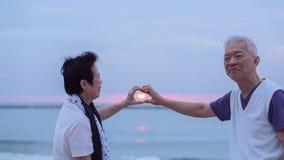 Asian senior couple together at sunrise beach. New year, new cha Stock Image