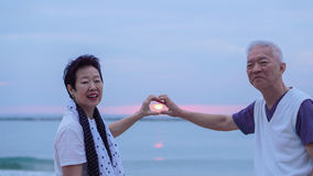 Asian senior couple together at sunrise beach. New year, new resolution concept Stock Images